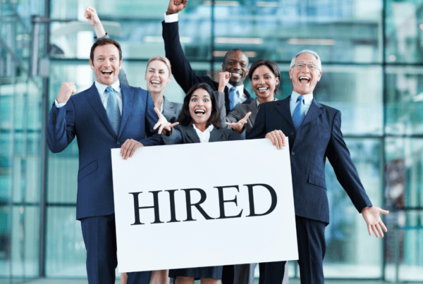 """Office team holding a """"hired"""" sign"""
