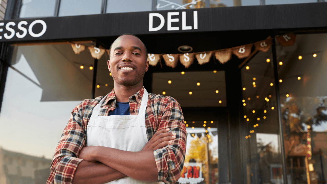 Business owner standing in front of his deli shop