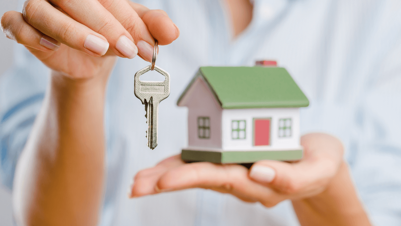Woman holding a key and house in her hands