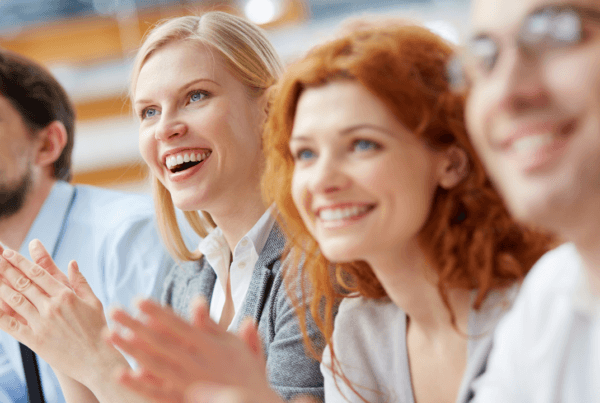 An office team clapping with excitement at another approval