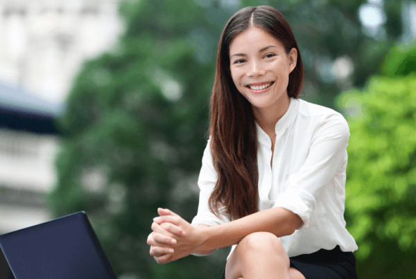 Business woman sitting outside smiling with her laptop